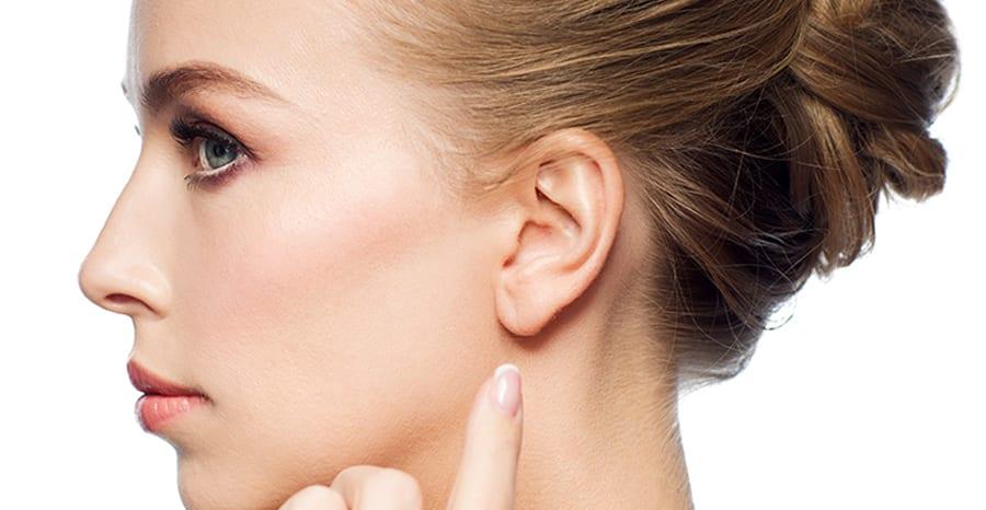 imagen de una mujer señalándose una oreja tras una cirugía de otoplastia.